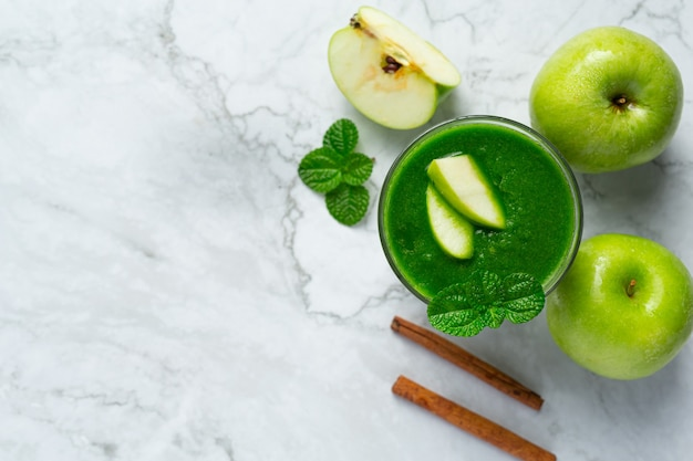 Glass of green apple healthy smoothie put next to fresh green apples