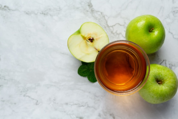 Glass of green apple healthy tea put next to fresh green apples