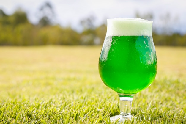 Glass of green beer on the lawn to celebrate st. patricks day.