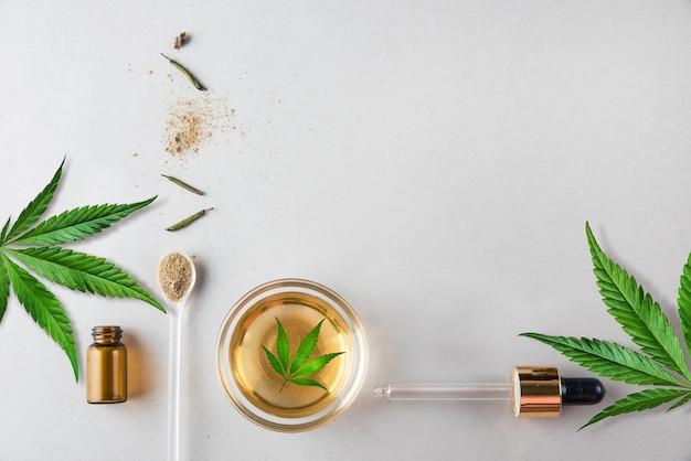 유리 녹색 병 및 cbd 오일과 대마초 잎이 배경에 있는 피펫은 최소한의 개념 평면 위치에 있습니다