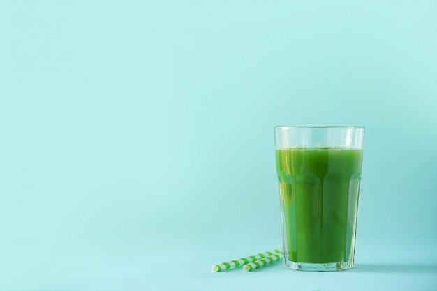 Glass of green celery smoothie on blue background