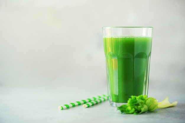 Glass of green celery smoothie on grey concrete background