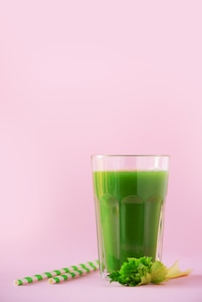 Glass of green celery smoothie on pink background