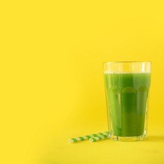Glass of green celery smoothie on yellow background