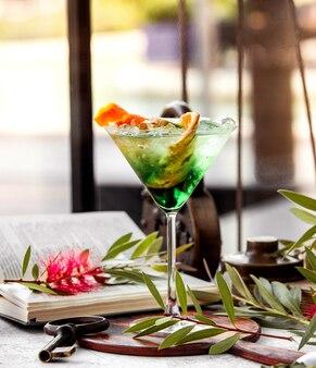 Glass of green cocktail garnished with orange zest banana peel and kiwifruit