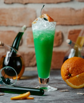 A glass of green cocktail with ice cubes and orange slices.