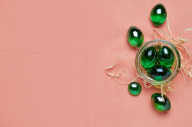 Glass green crystals in a glass dish on a scarlet cloth. the view from the top