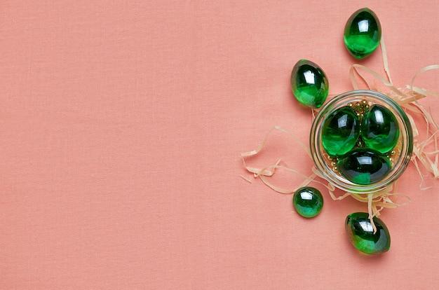 緋色の布の上のガラス皿のガラス緑色の結晶。上からの眺め