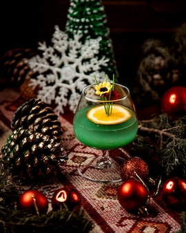 A glass of green drink garnished with orange slice and fake flowers around christmas decorations