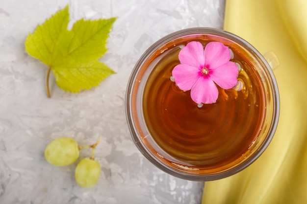 Glass of green grape juice with green textile and pink flower.  top view