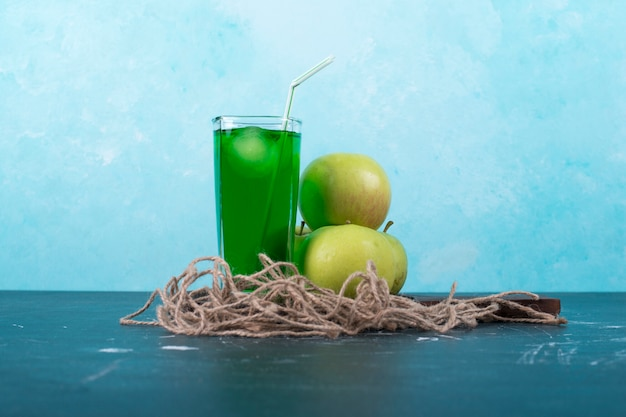 A glass of green juice with apples on wooden platter on blue.