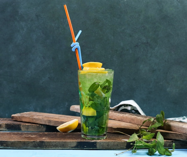 A glass of green mojito with lemon on a piece of wood.