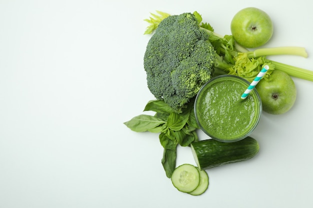 Glass of green smoothie and ingredients on white background, space for text