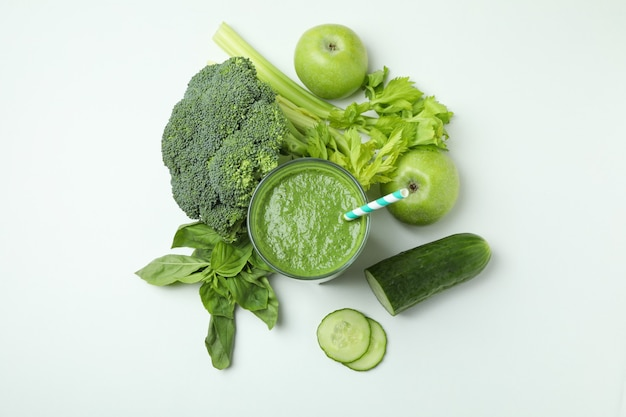 Glass of green smoothie and ingredients on white background, top view