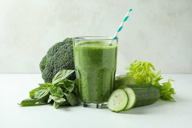 Glass of green smoothie and ingredients on white table