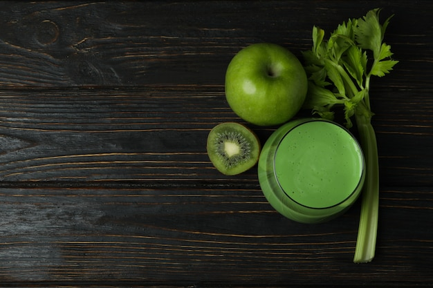 Glass of green smoothie and ingredients on wooden table