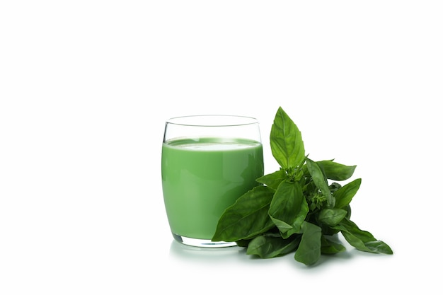 Glass of green smoothie and spinach isolated on white background