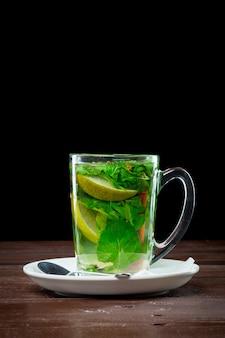Glass of green tea with lime, lemon, mint