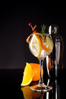 Glass of greyhound cocktail decorated with orange fruit at bright bar counter background.