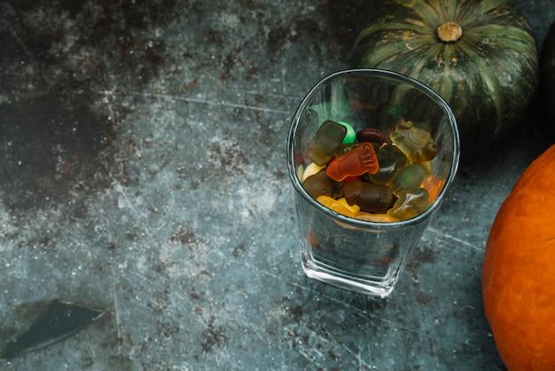 Bicchiere di gummies vicino zucche