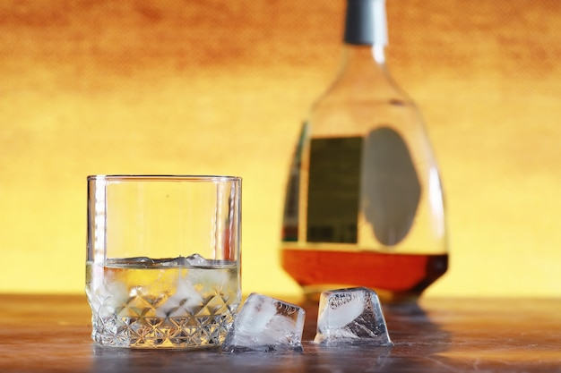 A glass of hard alcohol with ice on a bar counter. whiskey with soda in a glass. advertising alcoholic drink.