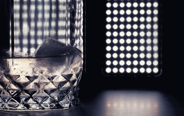 A glass of hard alcohol with ice on a bar counter whiskey with soda in a glass