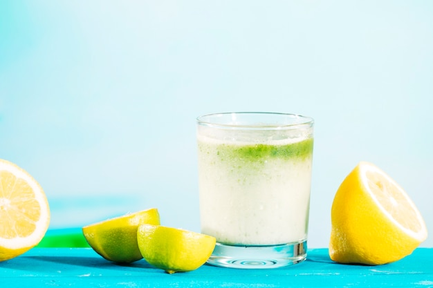 Glass of healthful green smoothie and sliced citrus