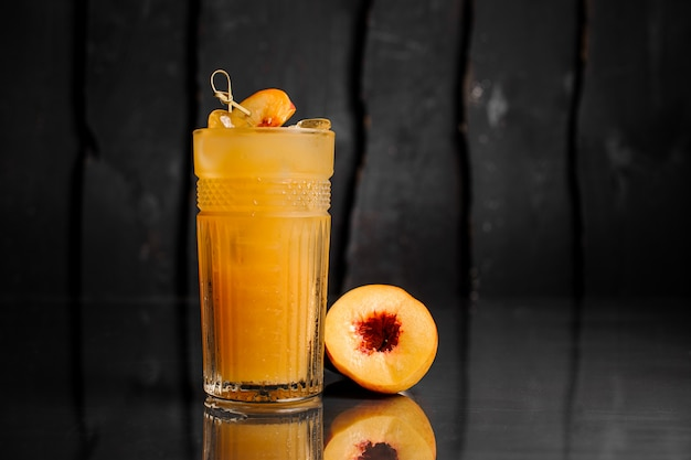 Glass of healthy peach cocktail decorated with pieces of peach