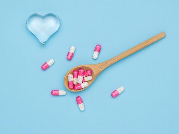 유리 심장 및 치료 캡슐과 나무로되는 숟가락. 심장 질환 치료의 개념.