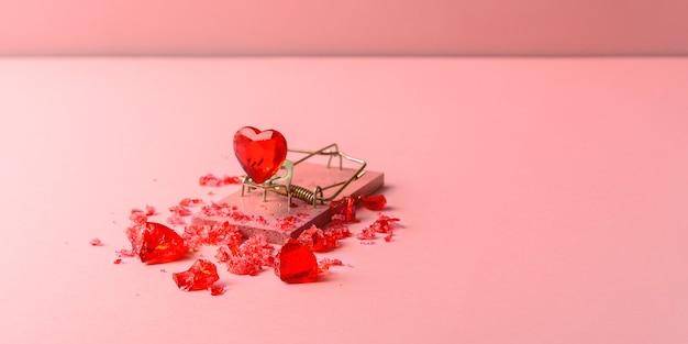 복사 공간이 있는 분홍색 배경에 쥐덫에 유리 심장. 발렌타인 데이를 위한 창의적인 컨셉입니다.