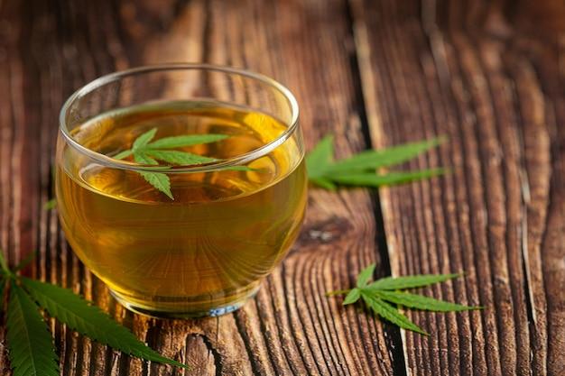 Bicchiere di tè di canapa con foglie di canapa messo sul pavimento di legno