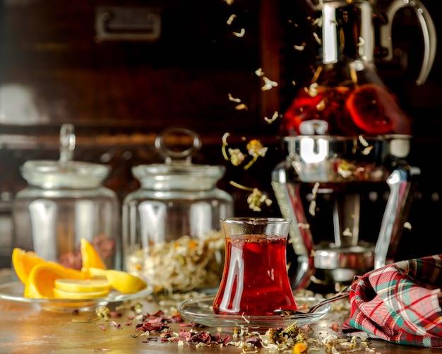 Glass of herbs tea next to lemon slices and glass tea pot