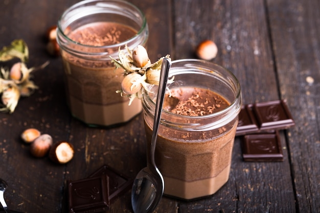 Glass of homemade yogurt with chocolate mousse and chocolate candy and spoon