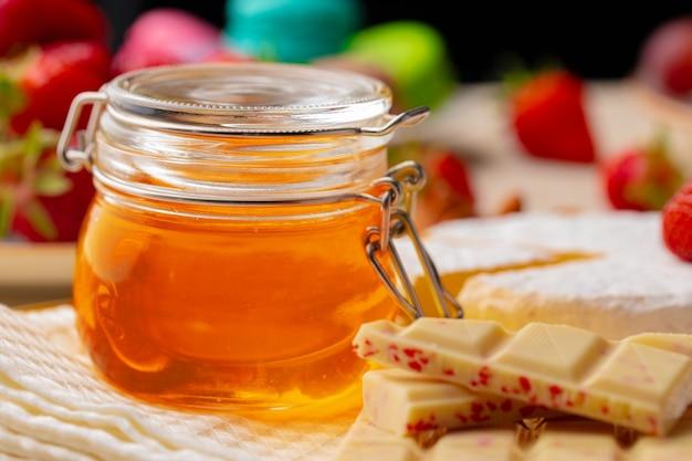 果物やお菓子の背景にガラスの蜂蜜の瓶
