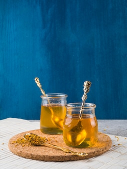 Glass honey pots with spoon on cork coaster