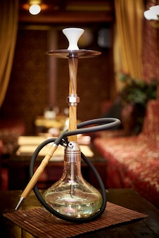 A glass hookah is on the table in the lounge bar