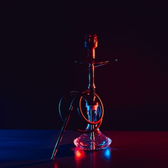 Glass hookah with a metal bowl with hot coals on a black background on a table in a restaurant