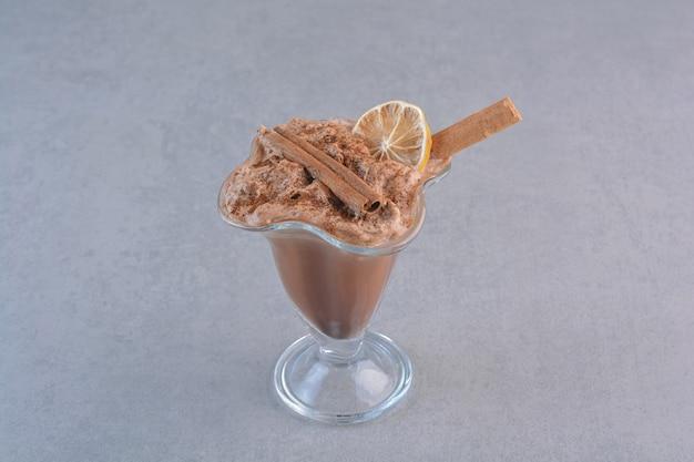 Un bicchiere di cioccolata calda decorata con bastoncini di cannella sul tavolo in pietra.