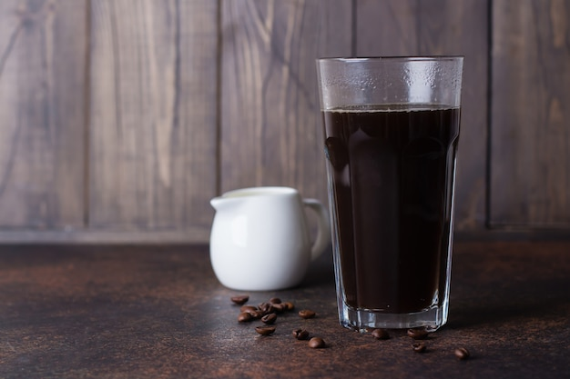 A glass of hot coffee espresso  with coffee beans