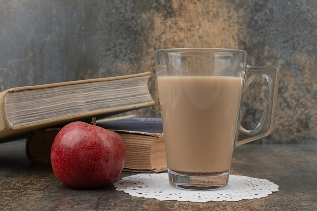 A glass of hot coffee with one red apple and books on marble wall.