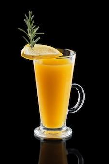 Glass of hot lemon tea with ginger and rosemary isoalted on black.