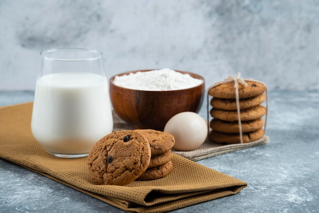 A glass of hot milk with delicious cookies on a gray table.