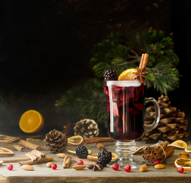 Glass of hot mulled wine with ingredients