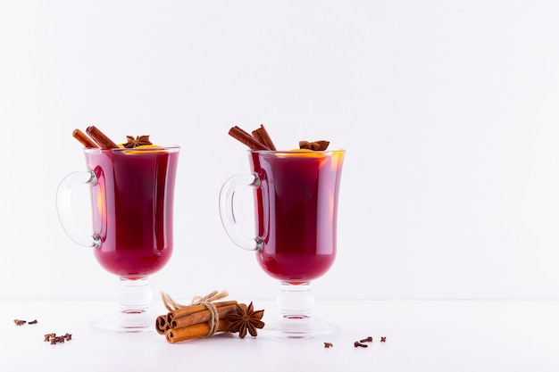 Glass of hot mulled wine with spices on white background