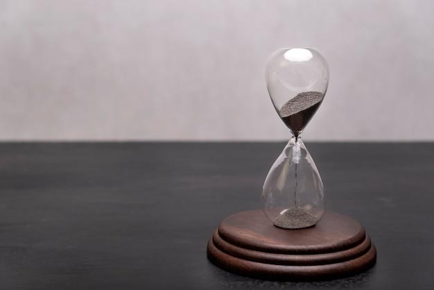 スタンドにガラスの砂時計。時間がなくなっています。時間管理。テキストの場所。