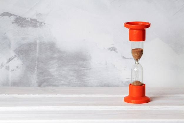コンクリートの壁の背景にガラスの砂時計。コピースペース