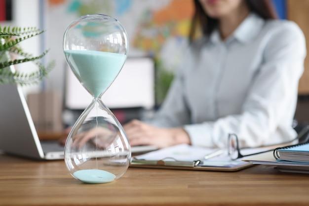 ノートパソコンのクローズアップで働く女性の背景に立っているガラスの砂時計