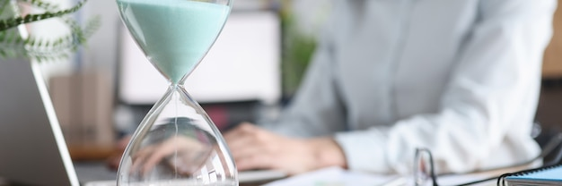 Стеклянные песочные часы, стоящие на фоне женщины, работающей на ноутбуке крупным планом