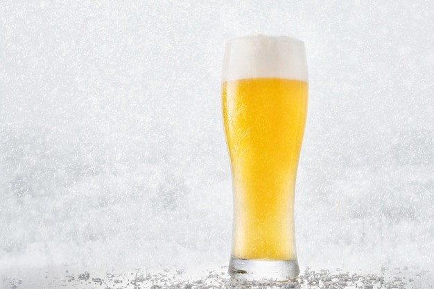 Glass of ice beer against the backdrop of a winter landscape