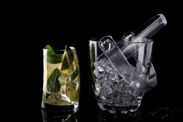 Glass ice bucket and mohito cocktail in glass isolated on black